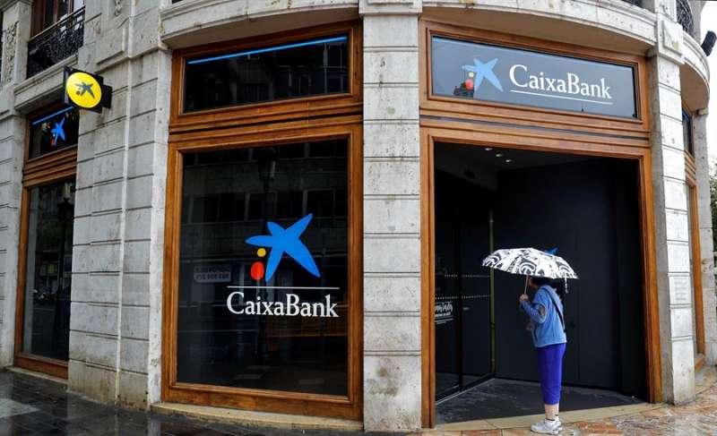 Una mujer observa el interior de una sede de Caixabank. EFE/Manuel Bruque/Archivo