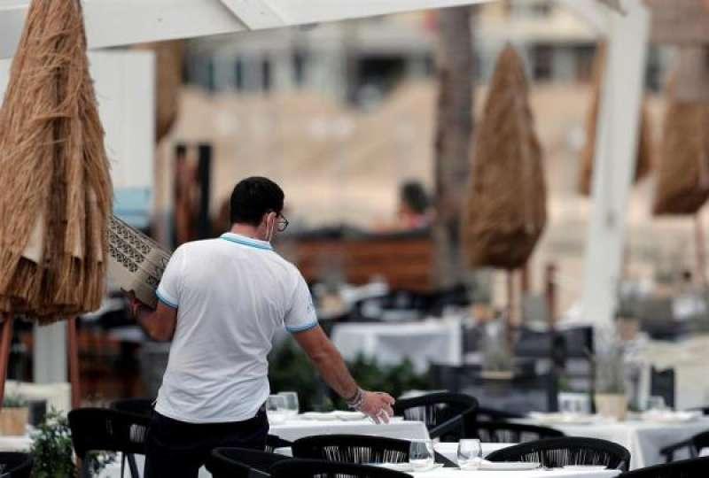 Un camarrero prepara unas mesas de una terraza. EFE/Kai Försterling/Archivo./ EPDA