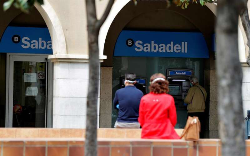 Varias personas esperan ante una sucursal del Banco Sabadell en una imagen de archivo EFE/Manuel Bruque