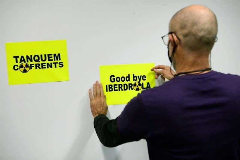 Un miembro de Tanquem Cofrents pega unas pegatinas en un acto informativo. EFE/ Biel Aliño
