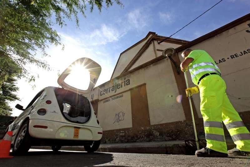 Un operario de los servicios municipales del Ciclo Integral del Agua limpia un imbornal en una calle de Valencia. EFE/Manuel Bruque/Archivo.