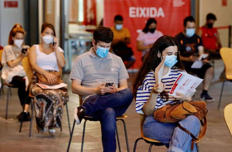 Varios jóvenes esperan en el Auditori de Castelló su turno para recibir la primera dosis de la vacuna.