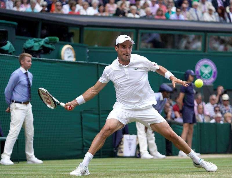 El castellonense Roberto Bautista devuelve la bola al serbio Novak Djokovic durante su duelo de semifinales en Wimbledon. EFE