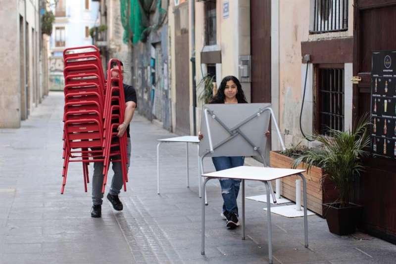 Dos trabajadores de un local de ocio recogen sillas y mesas de la terraza en València. EFE/ Biel Aliño