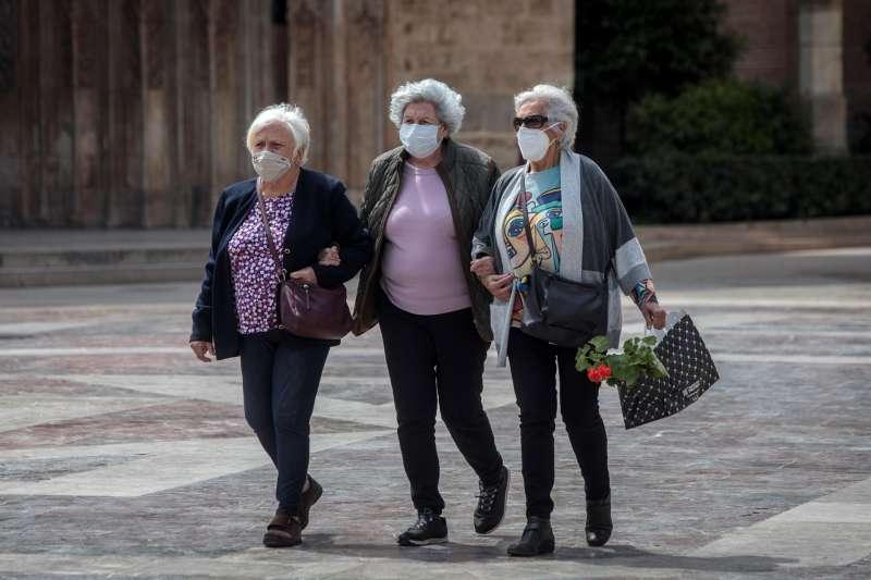 Tres señoras caminan cogidas del brazo en una céntrica plaza de València.