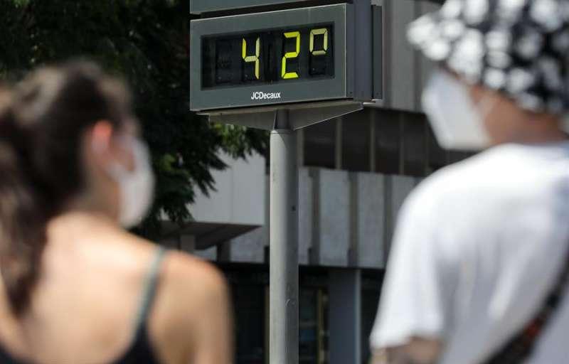 Varias personas pasan ante un termómetro urbano que marca 42 grados centígrados este viernes en Valencia. EFE