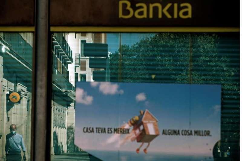 Vista de una oficina de Bankia y otra de CaixaBank reflejada en el cristal en el centro de L