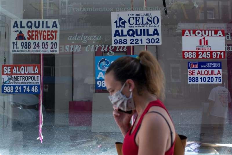 Una mujer pasea junto a un escaparate con carteles de alquiler