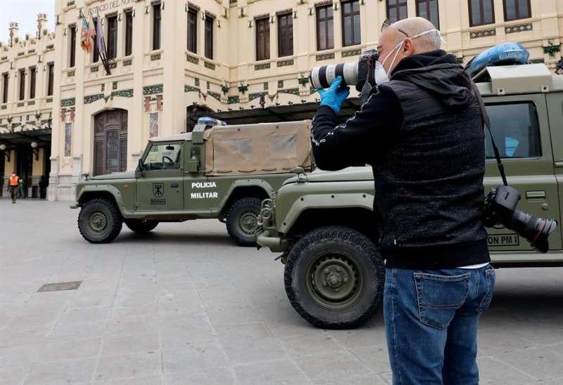 Imagen de archivo de un fotoperiodista protegido con mascariila y guantes en València. EFE