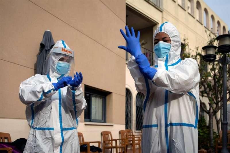 Dos profesionales sanitarias se ponen un EPI. EFE