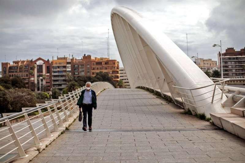 Una persona con mascarilla camina por el puente de la Exposición de València. EFE