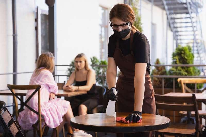 Una camarera desinfecta las mesas del restaurante antes del cierre de la hostelería.