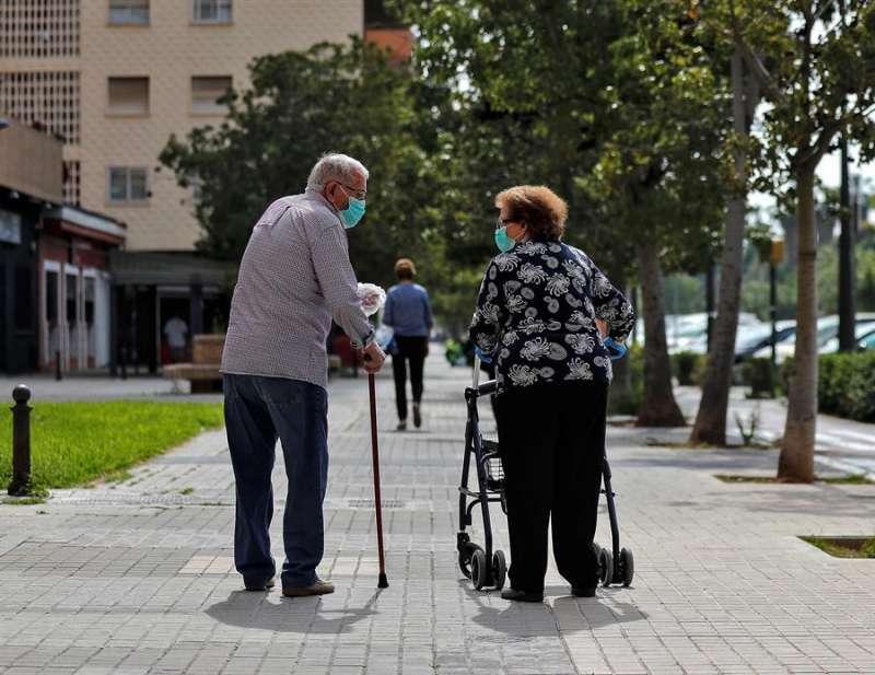 Dos personas mayores conversan mientras pasean en València./ EFE / Manuel Bruque/ Archivo