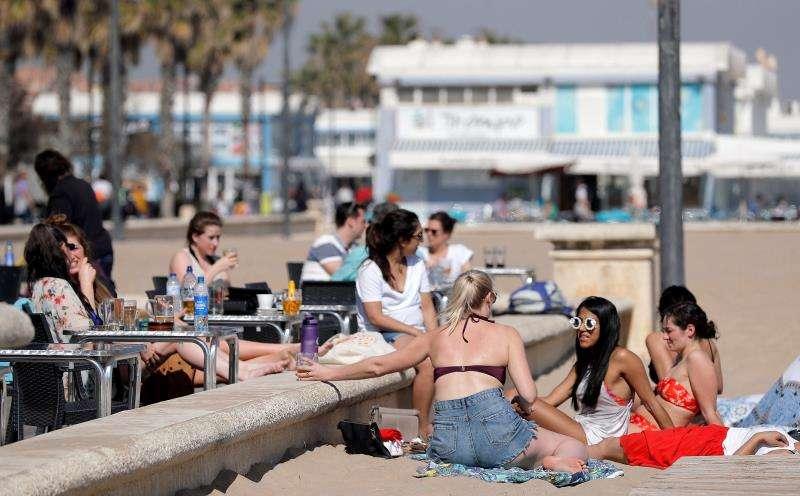 Varias jóvenes disfrutan del sol y las temperaturas en la playa de la Malvarrosa de València. EFE