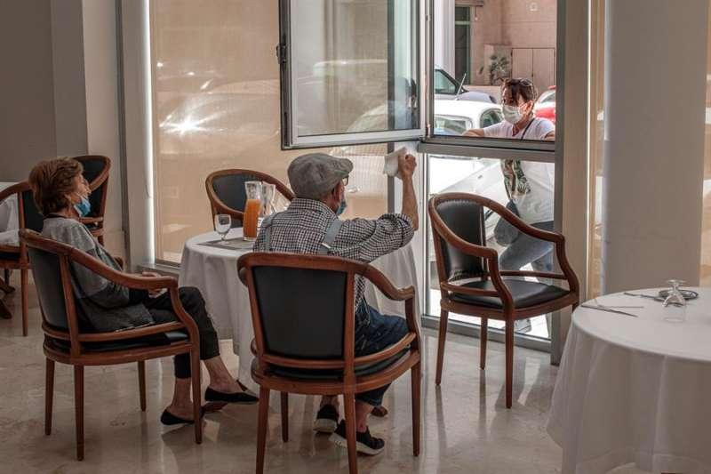 Una persona conversa con sus padres a través de una ventana habilitada en la residencia de mayores Ballesol Patacona, en Valencia. EFE