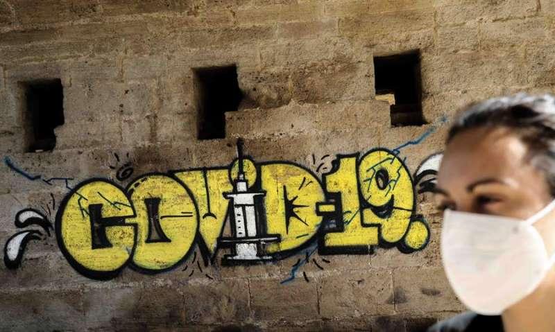 Una persona con mascarilla pasa ante un grafiti en València. EFE/Archivo