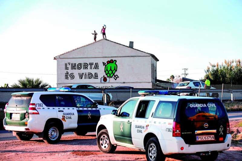 Activistas de asociaciones ecologistas, apostados en el tejado, tratan de impedir el derribo de una alquería en la huerta de Alboraia. / EFE