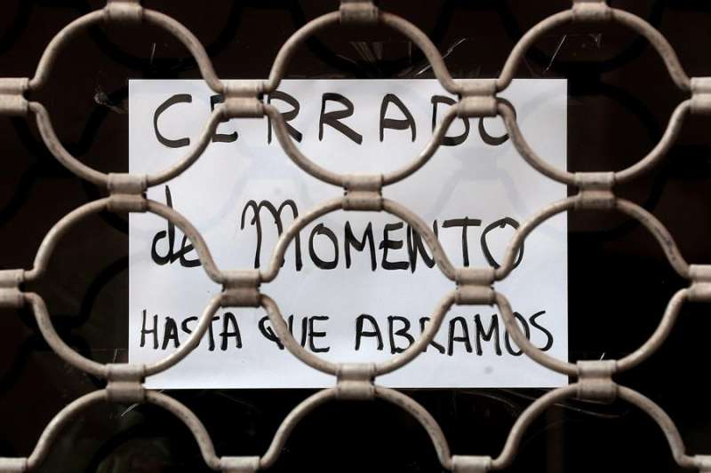 Detalle de un cartel colgado en la fachada de una tienda con el lema