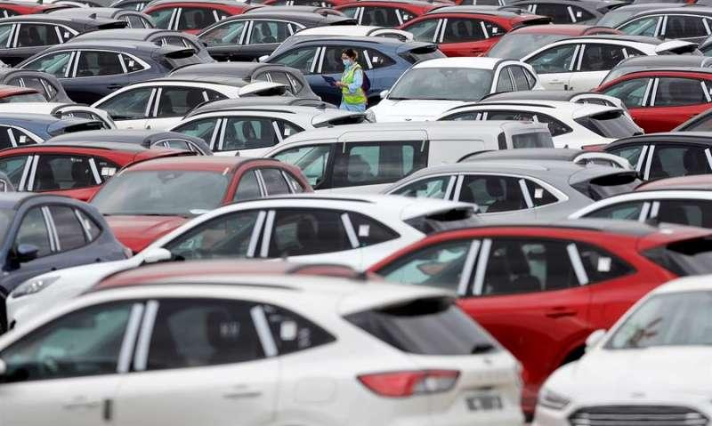 Una trabajadora de Ford camina entre automóviles aparcados en el exterior de la planta en Almussafes, en una imagen reciente. EFE