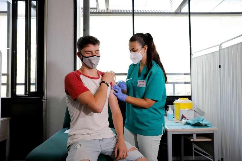 Un alumno de la Universitat de València recibe una dosis de la vacuna contra la covid