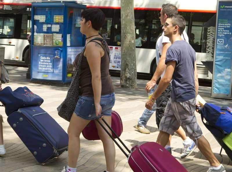Varios jóvenes turistas arrastran sus maletas camino a su hotel. EFE