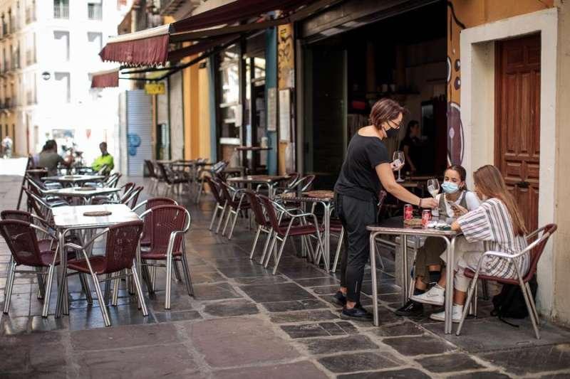 Una camarera atiende una mesa de una terraza en el centro de València. EFE
