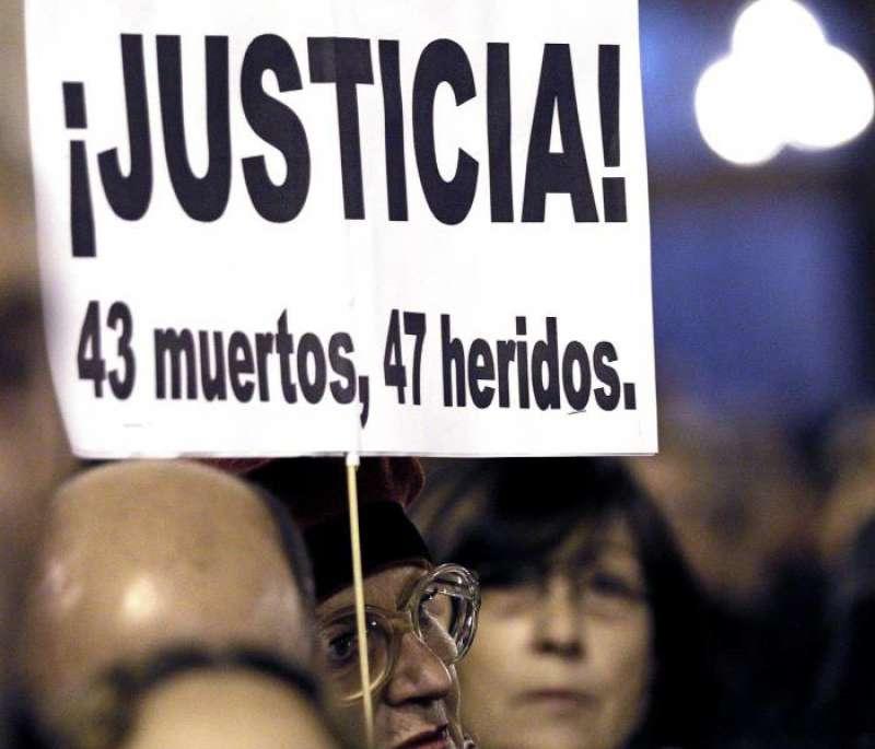 Una mujer muestra un cartel recordando el número de víctimas y heridos del accidente de Metro del 3 de julio de 2006. EFE/Archivo