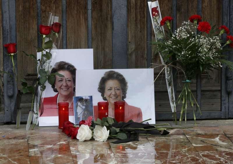 Una persona se para ante unas fotografías y flores colocadas por personas anónimas en uno de las puertas del Ayuntamiento de València en memoria de la exalcaldesa Rita Barberá.