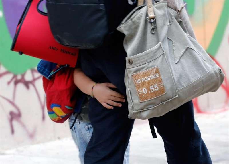 Un niño junto a su madre en el primer día de clase. EFE