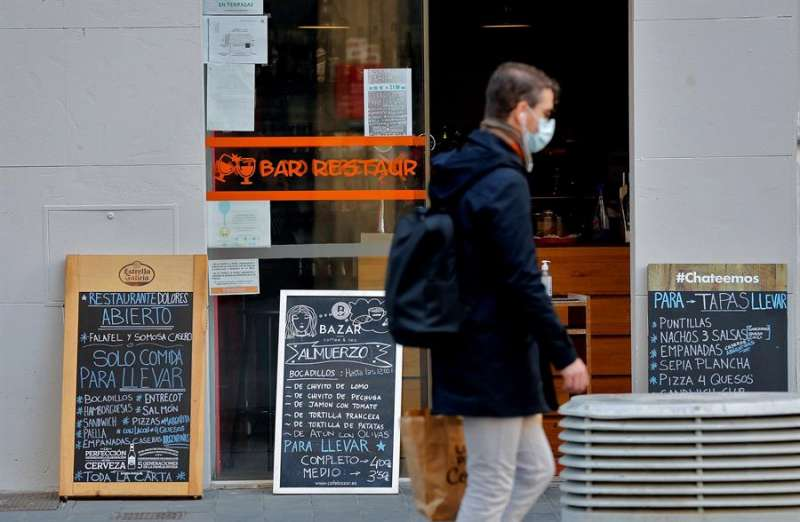 En la imagen, un hombre pasa ante un restaurante cerrado al público que muestra su carta y menús para llevar. EFE