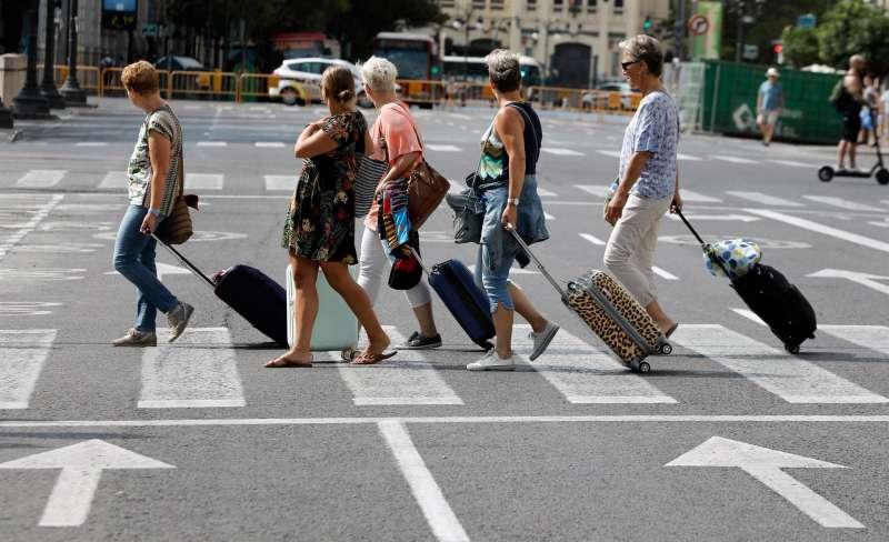 En la imagen, varios turistas extranjeros arrastran sus maletas tras abandonar un hotel en Valencia.