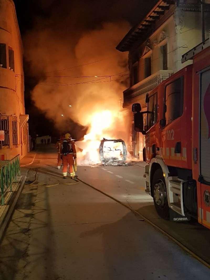 Los bomberos, junto a los coches incendiados. EPDA