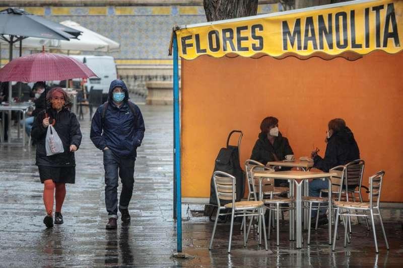 Dos personas en la terraza de un bar protegidas de la lluvia por un toldo de un puesto de flores