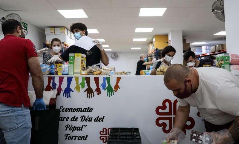 Parte del legado se ha destinado a asociaciones de voluntariado juvenil. En la imagen, varios voluntarios atienden a personas que necesitan comida. / EFE