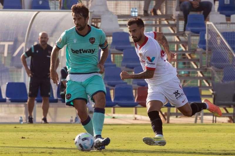 El defensa del Levante Unión Deportiva Coke (i) controla el balón ante el delantero del Sevilla Fútbol Club Suso Fernández (d), durante unl partido amistoso. EFE/Archivo