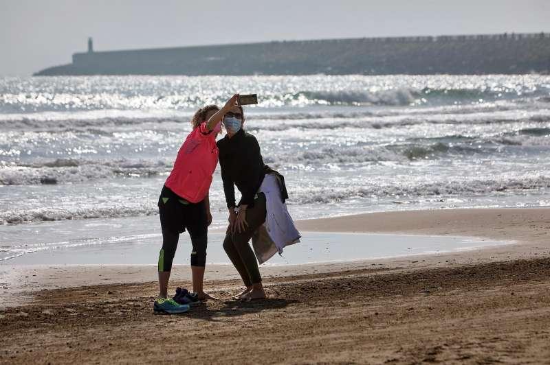 Imagen de archivo de dos turistas, con mascarilla, haciéndose un selfi en la playa de Gandia (Valencia).EFE