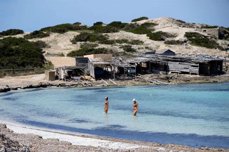 Dos personas se bañan en la playa de Ses Illetes, estos días en Formentera. EFE/Sergio G. Canizares