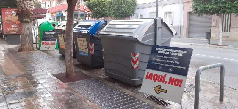 Carteles informativos junto a contenedores tradicionales en Paterna.