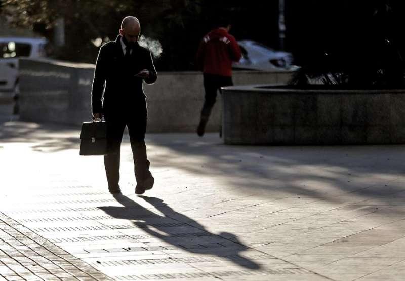 Un hombre consulta su teléfono móvil camino de la oficina. EFE/Manuel Bruque/Archivo