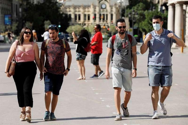 Varias personas sin mascarilla caminan por el centro de València. EFE