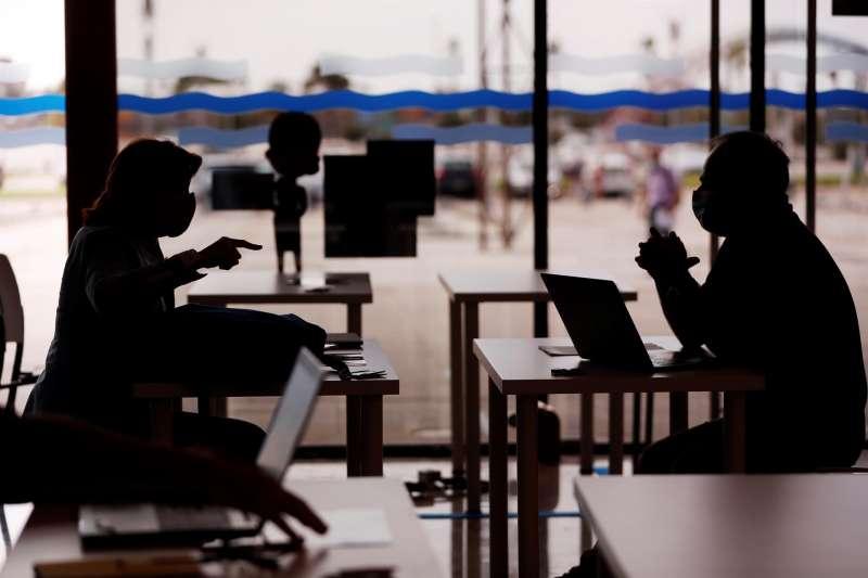 Unas personas dialogan durante una feria para startups.