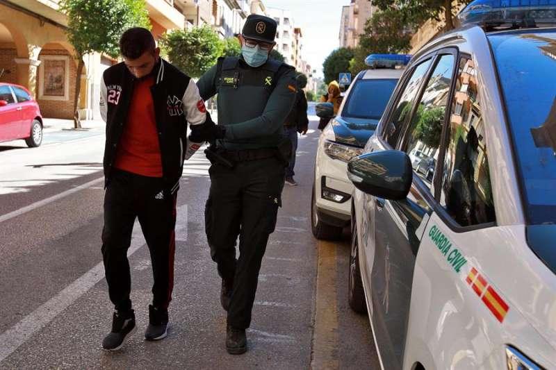 Un agente de la Guardia Civil traslada al Juzgado de Instrucción número 1 de Ontinyent a uno de los detenidos. EFE/Natxo Francés