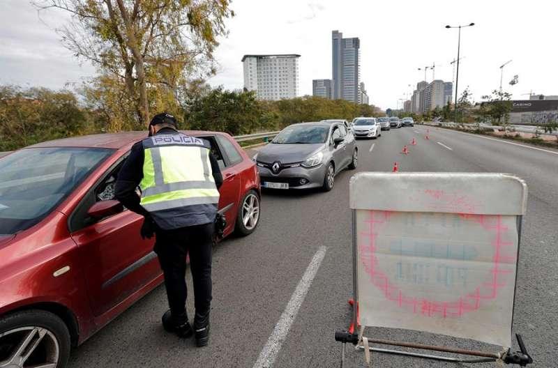 Un agente de la Policía Nacional pregunta a una conductora el motivo de su desplazamiento en uno de los controles establecidos en la ciudad de Valencia. EFE/Manuel Bruque