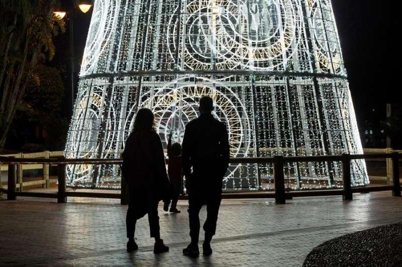 Una pareja y su hijo observan un árbol de navidad iluminado en la Plaza de la Marina, en Málaga. EFE/Daniel Pérez/Archivo