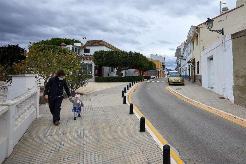 Una mujer pasea con un bebé en la localidad valenciana de Guardamar de la Safor, municipio que no ha notificado aún ningún caso positivo por coronavirus desde el inicio de la pandemia. EFE/Natxo Francés