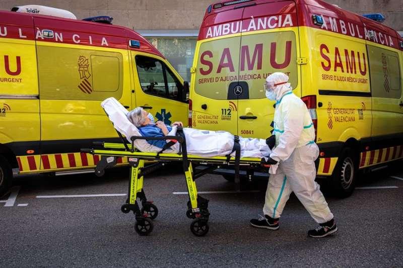 Un sanitario con equipo de protección especial traslada a un paciente de una ambulancia a urgencias del Hospital Clínico de València. EFE