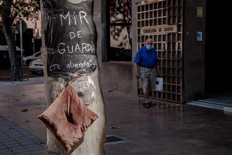 Una persona pasa ante la Conselleria de Sanidad donde se puede ver una bolsa de basura usada a modo de bata con el lema
