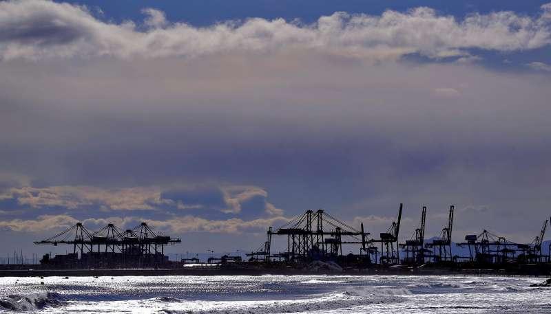 La silueta de las grúas del Puerto de Valéncia se observan desde la playa de La Patacona de Alboraya.