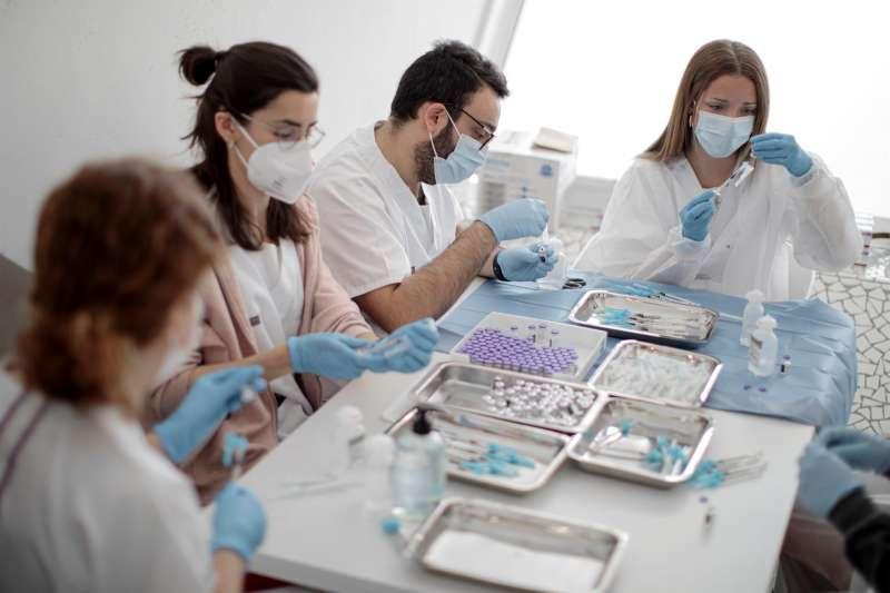 Varios sanitarios preparan vacunas contra la covid-19