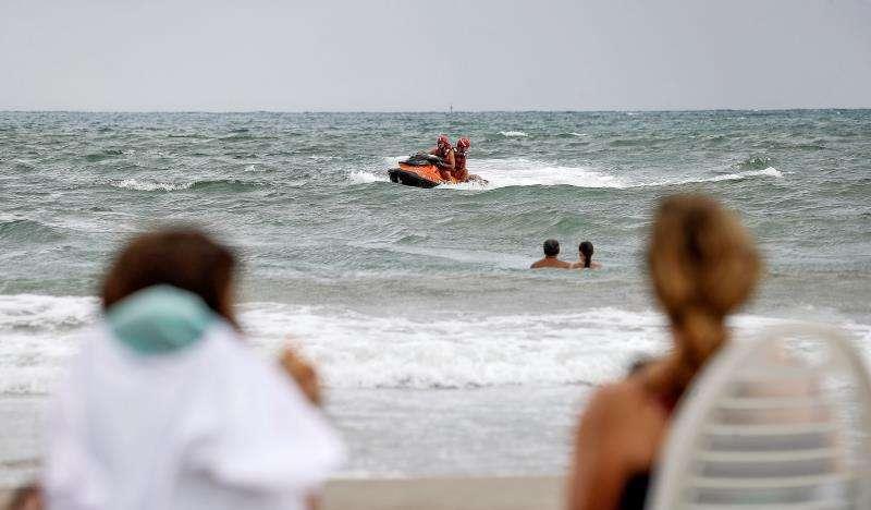 Dos mujeres observan desde la orilla una intervención de dos socorristas.